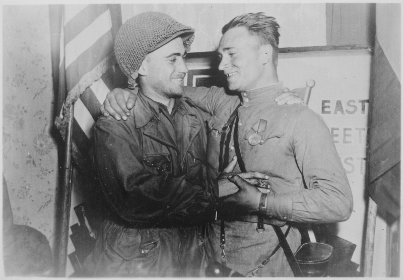 Happy_2nd_Lieutenant_William_Robertson_and_Lt._Alexander_Sylvashko _Russian_Army _shown_in_front_of_sign_(East_Meets..._-_NARA_-_531276.tif
